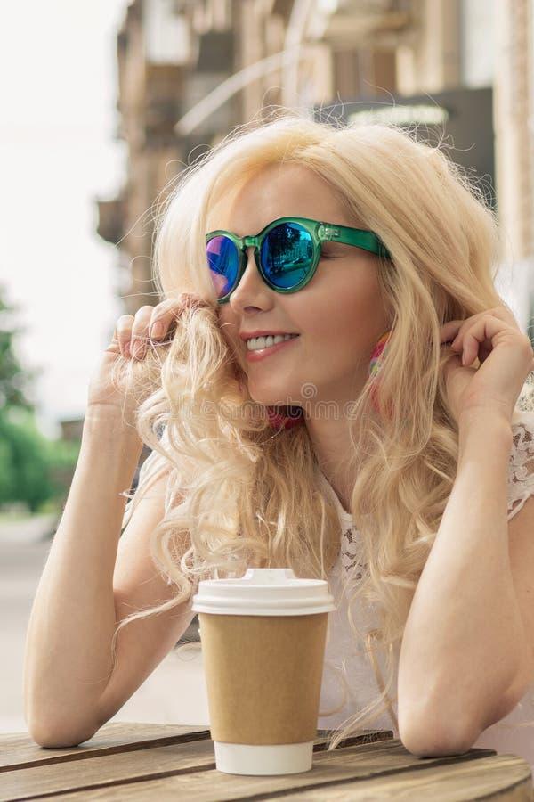 A menina loura bonita na cidade está bebendo o café Sessão de foto da rua Copo cinzento com uma tampa branca e um lugar para o lo fotografia de stock royalty free