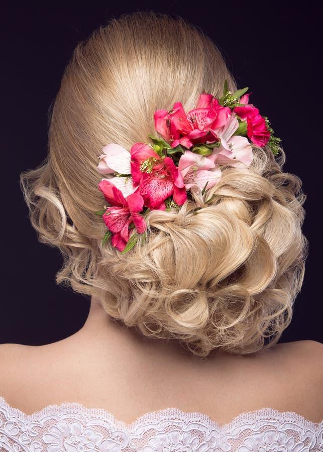 Menina loura bonita na imagem da noiva com as flores roxas em sua cabeça Face da beleza Opinião traseira do penteado imagem de stock