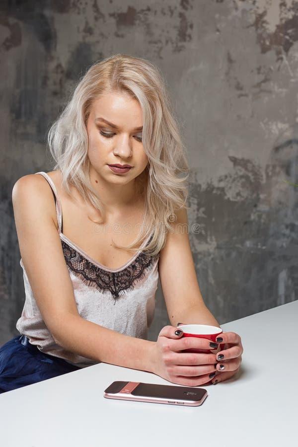 A menina loura bonita na roupa home está usando um smartphone foto de stock