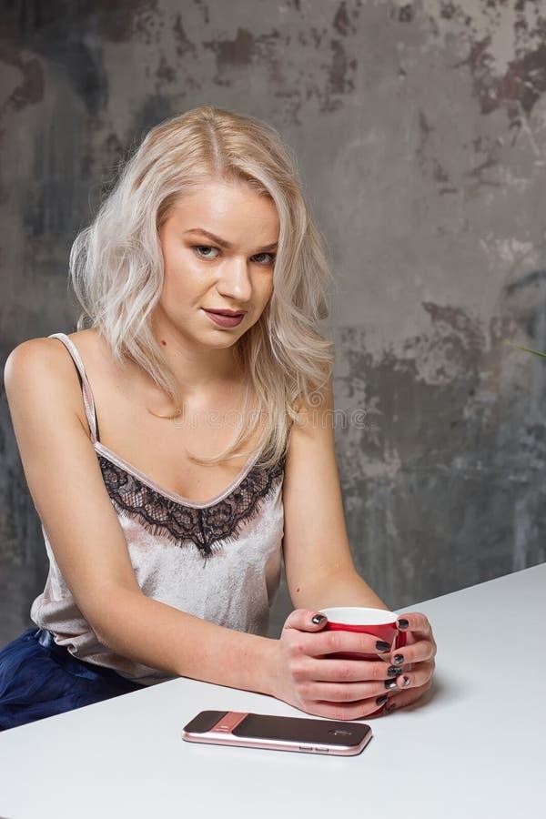 A menina loura bonita na roupa home está usando um smartphone fotografia de stock