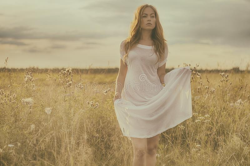 Menina loura bonita no campo verde com flores Cena rural fotografia de stock