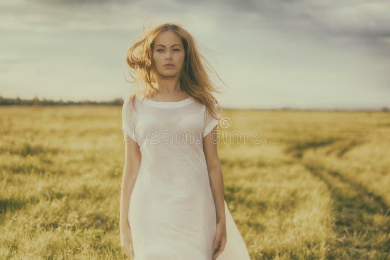 Menina loura bonita no campo verde com flores Cena rural imagens de stock