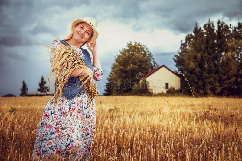 Menina loura bonita no chapéu no campo de trigo imagem de stock royalty free