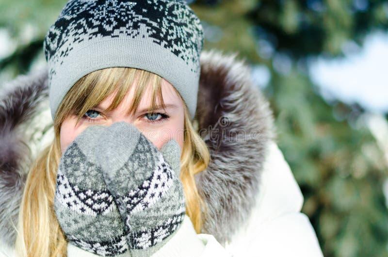 A menina loura bonita no chapéu e nos mitenes cobre sua cara fora no frio foto de stock