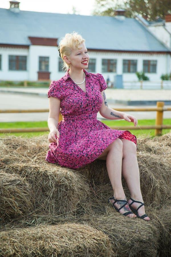 Menina loura bonita no estilo do pino-acima em um vestido brilhante no feno fotografia de stock royalty free
