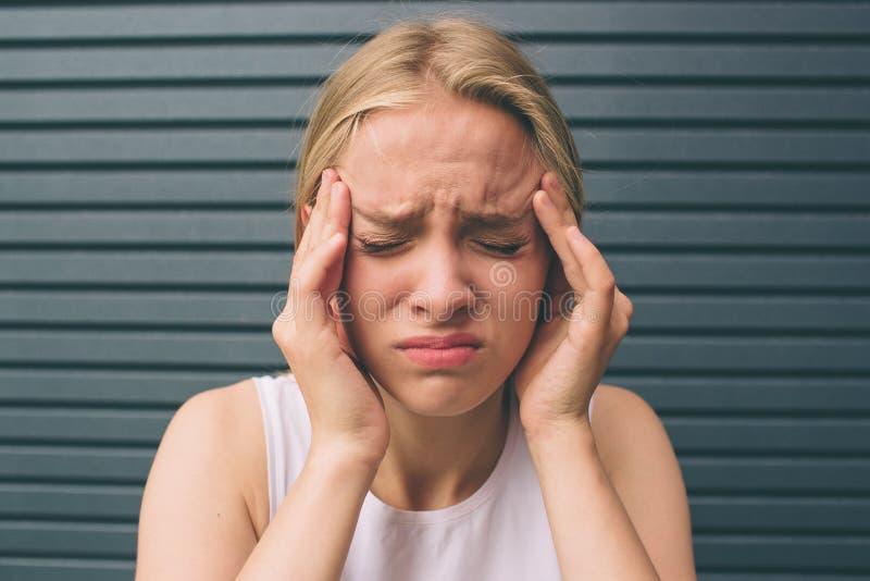 Menina loura bonita no fundo, mulher gritando irritada, dor de cabeça Retrato de uma mulher forçada que guarda principal dentro foto de stock royalty free