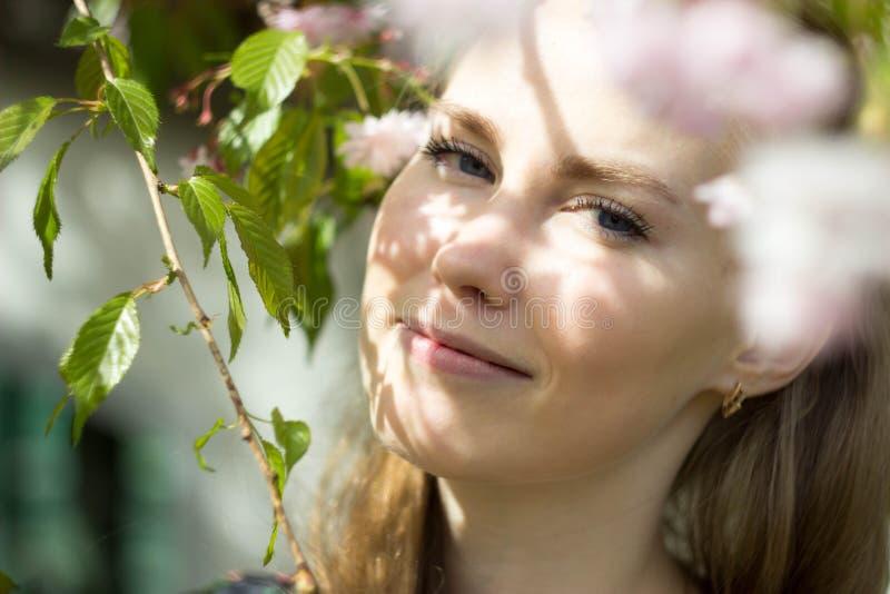Menina loura bonita no jardim da flor imagem de stock