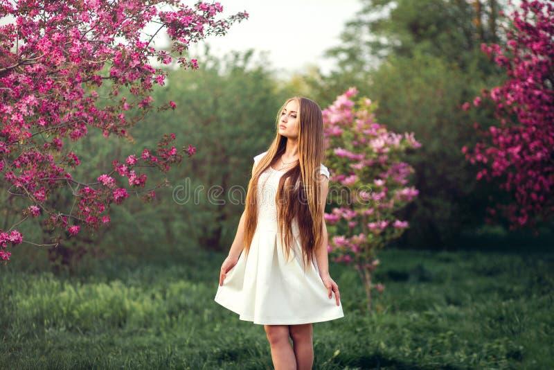A menina loura bonita no pêssego cor-de-rosa e sakura jardinam A menina bonita fora salta o retrato, jovem mulher com flores imagem de stock royalty free