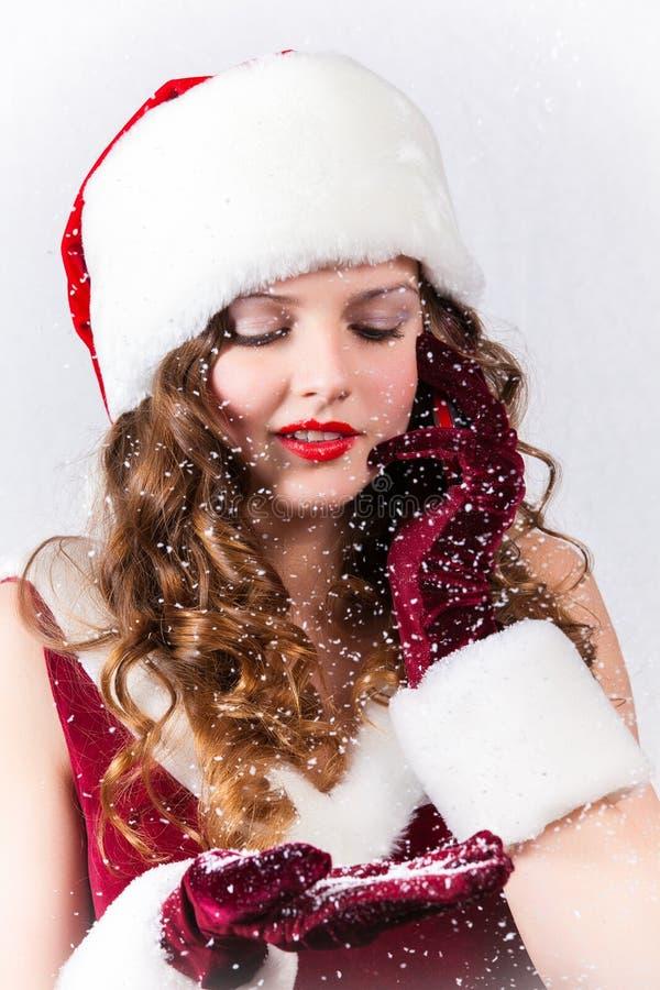 A menina loura bonita no xmas veste-se com o telefone celular no branco imagem de stock royalty free