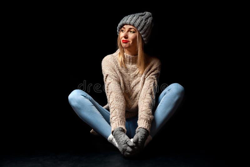 A menina loura bonita nova em luvas e no chapéu feitos malha no cinza, calças de ganga, camiseta bege senta-se no assoalho em uma fotografia de stock