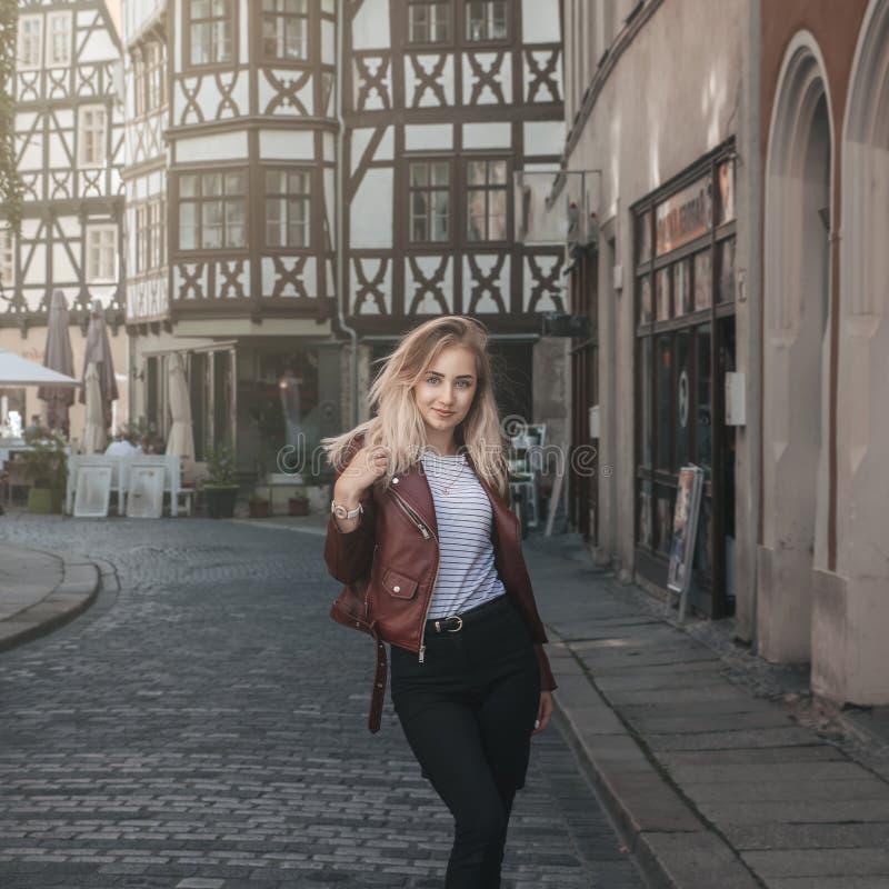 A menina loura bonita nova está andando ao longo do st velho do europeu foto de stock