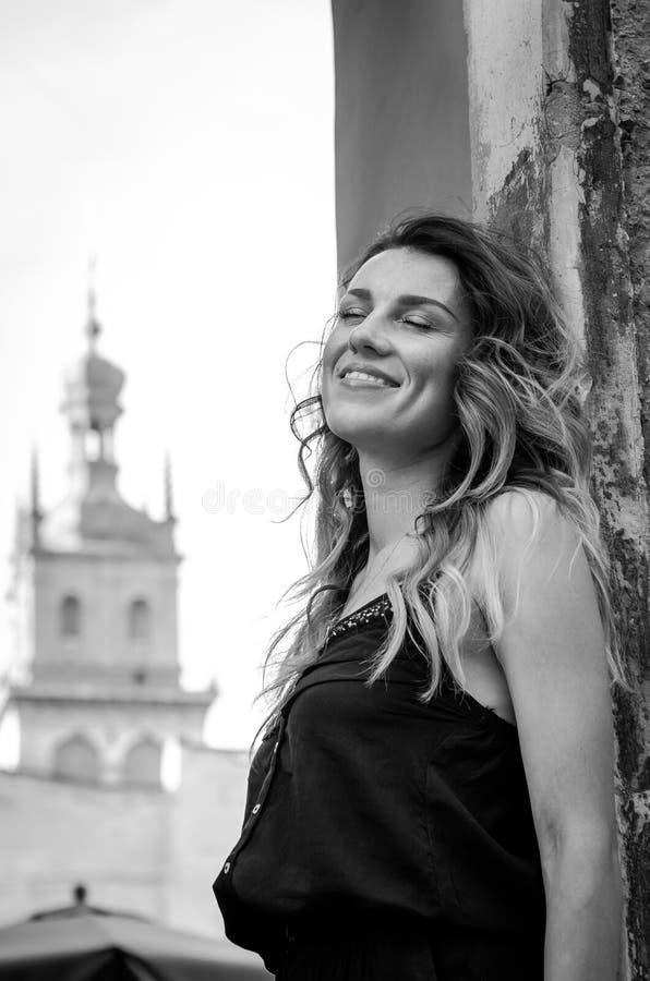 Menina loura bonita nova feliz com o cabelo longo que está na parede de pedra arruinada velha da fortaleza, dia ensolarado do ver imagens de stock royalty free
