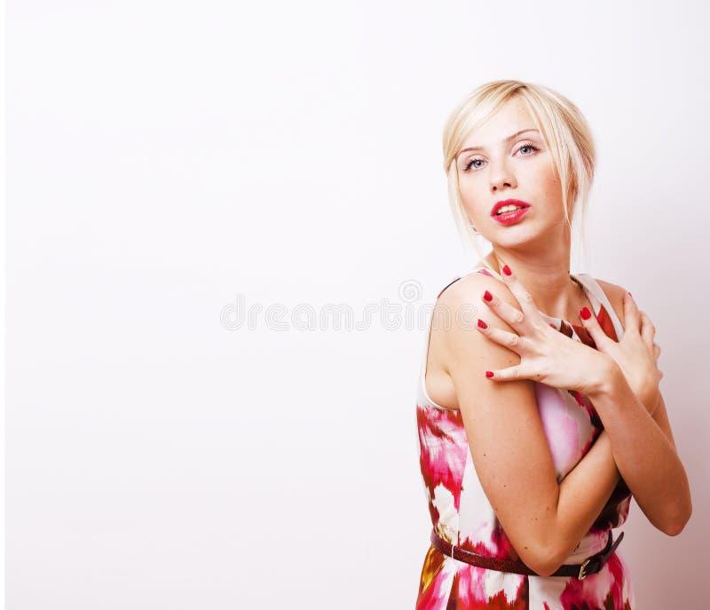 Menina loura bonita nova que apresenta algo no spac branco da cópia imagens de stock