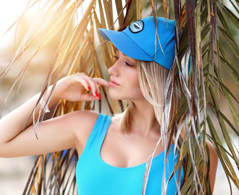 Menina loura bonita nova que levanta no recurso tropical da floresta da palmeira na veste e no tampão 'sexy' azuis do corpo fotos de stock royalty free