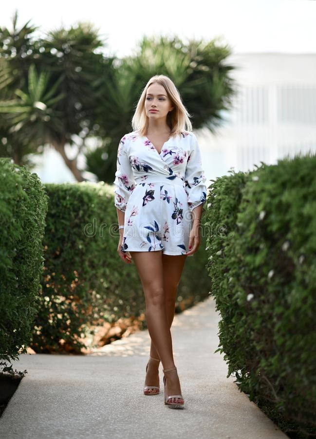 Menina loura bonita nova que levanta no recurso tropical da floresta no vestido ocasional branco foto de stock royalty free