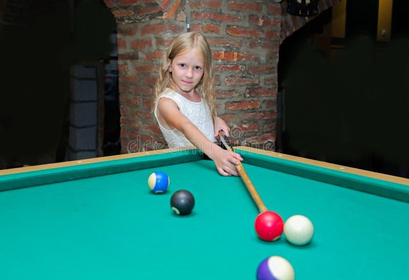 A menina loura bonita pequena aprende jogar bilhar, associação, sinuca, pirâmide do russo no clube da criança imagens de stock