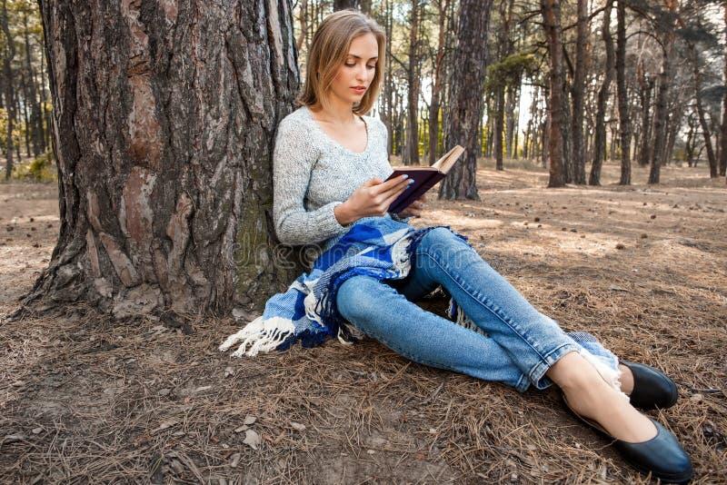 A menina loura bonita que descansa na floresta da mola ou do outono leu o livro e o assento com um livro Jovens caucasianos segur foto de stock