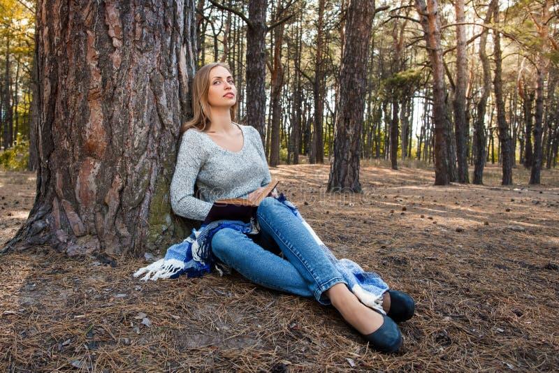 A menina loura bonita que descansa na floresta da mola ou do outono leu o livro e o assento com um livro Jovens caucasianos segur imagens de stock royalty free