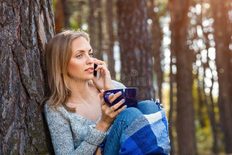 A menina loura bonita que descansa na floresta fala pelo telefone celular e, sentando-se com o copo do chá e do livro Caucasian s imagens de stock