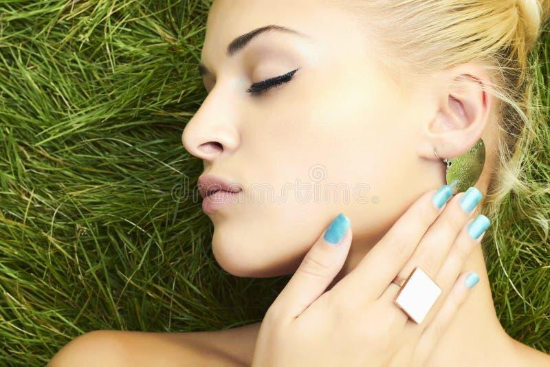 Menina loura bonita que dorme na grama verde. mulher da beleza fotos de stock royalty free