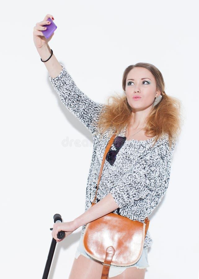 Menina loura bonita que faz o duckface do selfie com o saco do vintage em seu ombro Fim acima indoor foto de stock