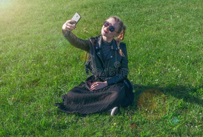 A menina loura bonita que senta-se em um gramado verde e faz o selfie fotografia de stock royalty free