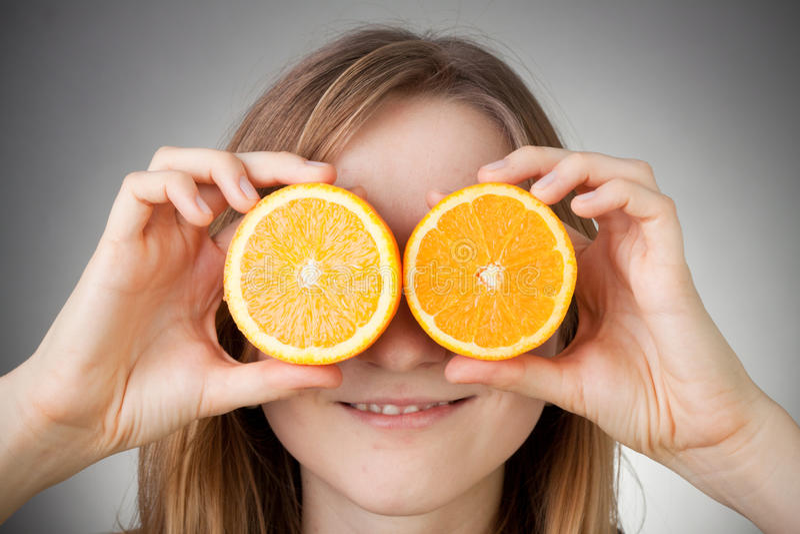 Menina loura bonita que usa a laranja como vidros fotografia de stock royalty free