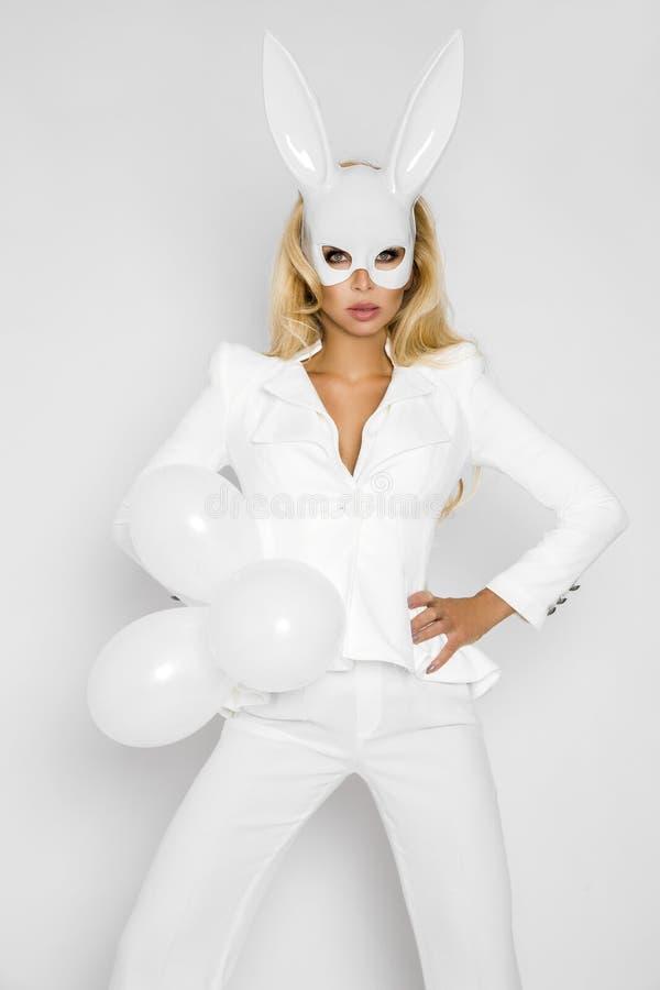 Menina loura bonita, 'sexy' da mulher na roupa branca elegante e em uma máscara e em um baloon brancos do coelho imagem de stock