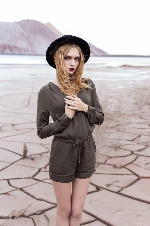 Menina loura bonita, 'sexy' que levanta nas montanhas em uma terra rachada em um chapéu negro com composição brilhante imagem de stock royalty free