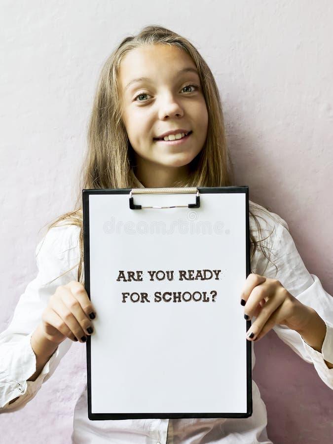 A menina loura bonito com texto é você redy para a escola Educação imagens de stock