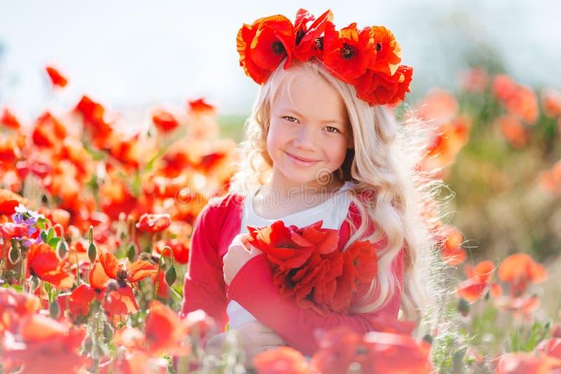 Menina loura bonito da criança no campo da papoila fotografia de stock royalty free
