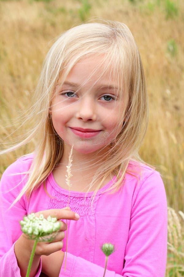 Menina loura bonito na grama. fotografia de stock