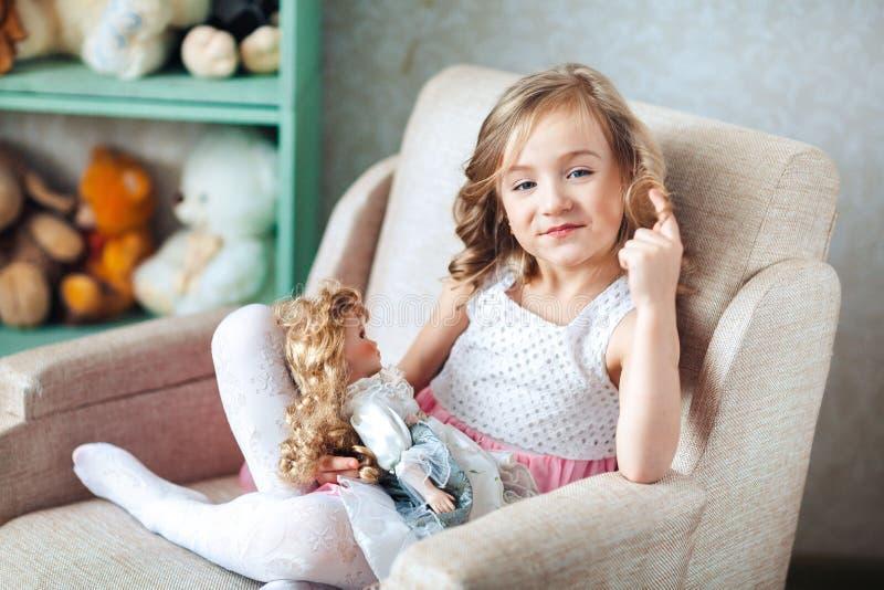 A menina loura bonito no vestido branco senta-se na cadeira e os sorrisos, dedo torcem o cabelo imagens de stock