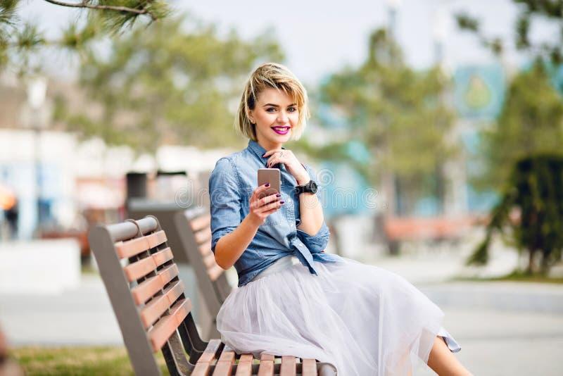 Menina loura bonito nova com o cabelo curto que senta-se em um banco de madeira que guarda um smartphone e um azul vestindo de so fotos de stock