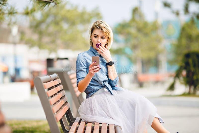 A menina loura bonito nova com o cabelo curto que senta-se em um banco de madeira olha o smartphone e obtém o azul vestindo choca foto de stock