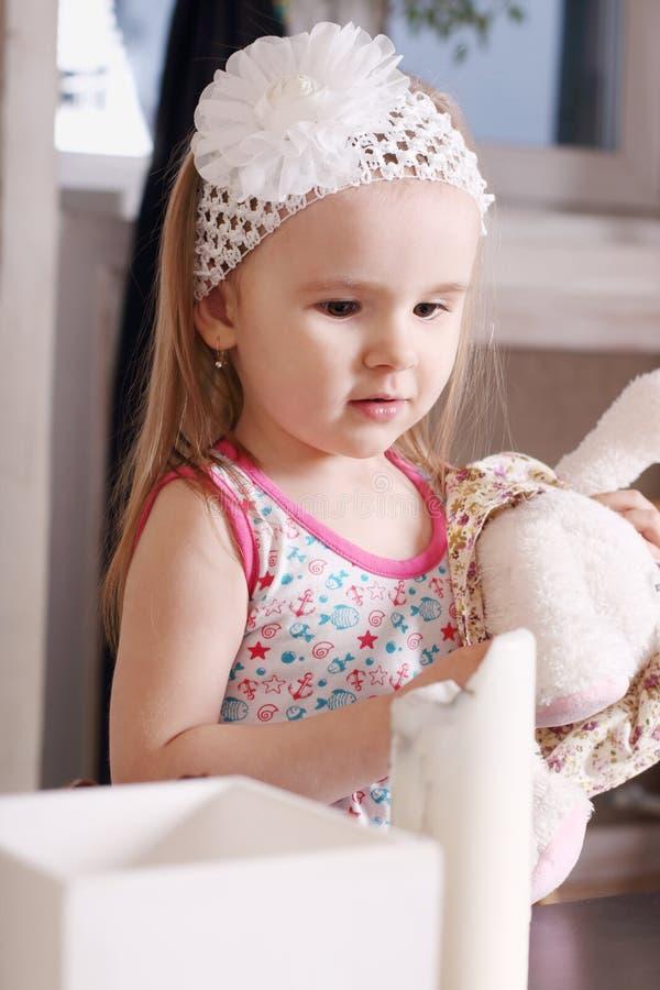 A menina loura bonito pequena com terra arrendada branca da faixa encheu o brinquedo fotos de stock