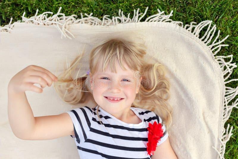Menina loura bonito pequena que encontra-se na cobertura sobre o gramado e o sorriso da grama verde Criança adorável que tem o di imagens de stock