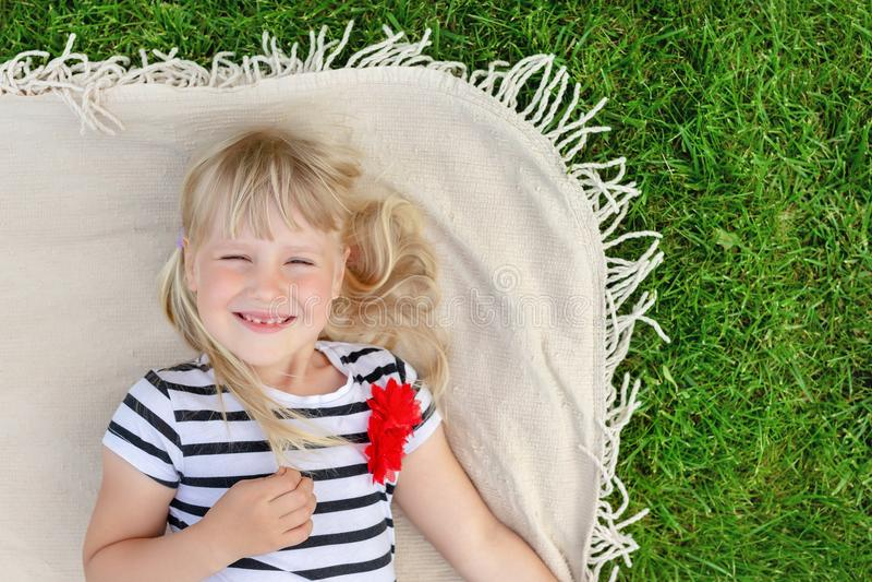 Menina loura bonito pequena que encontra-se na cobertura sobre o gramado e o sorriso da grama verde Criança adorável que tem o di foto de stock