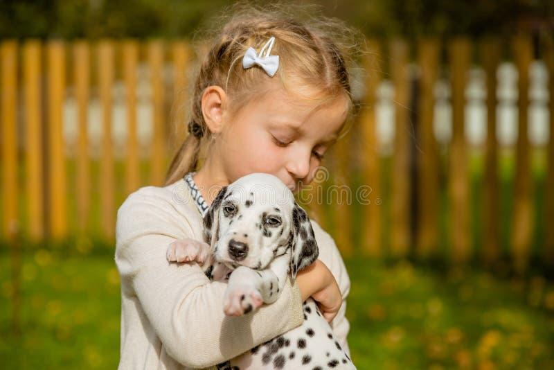 Menina loura bonito pequena que joga com seu outdoo Dalmatian do cachorrinho, no dia morno ensolarado do outono cuidado do concei foto de stock