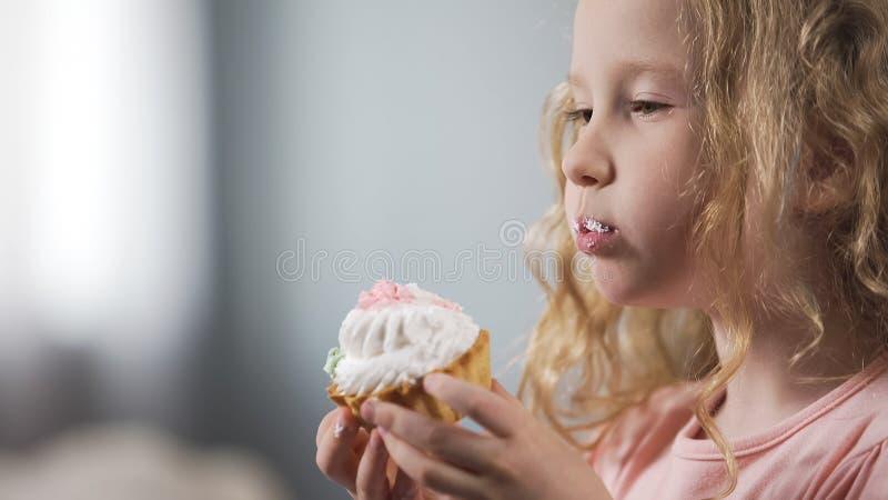 Menina loura bonito que come o bolo cremoso, o risco insalubre dos petiscos, da cárie e dos diabéticos fotografia de stock royalty free