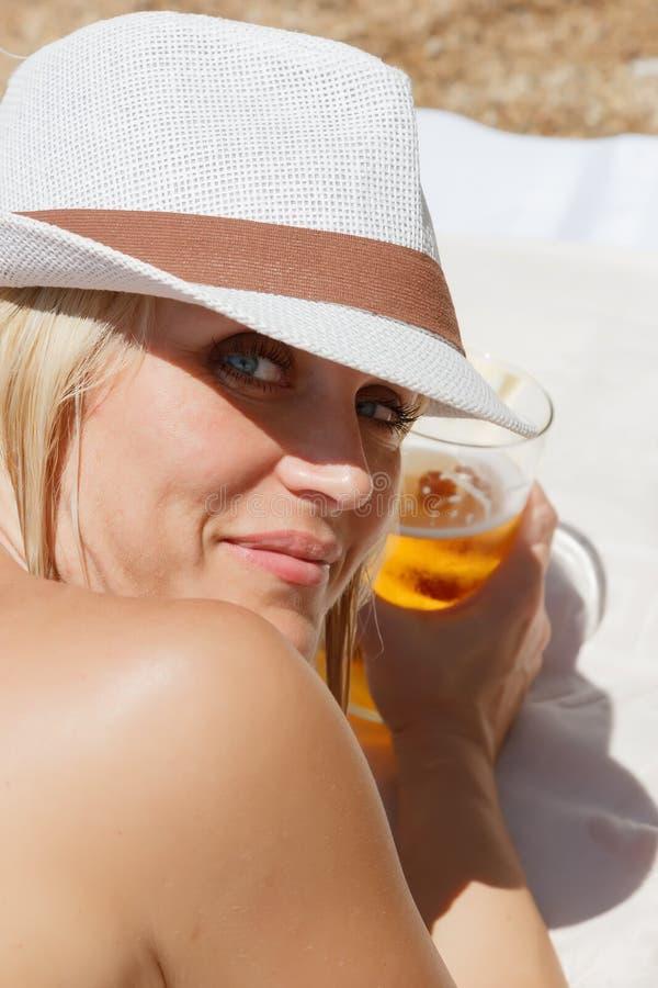 A menina loura branca em um chapéu branco toma sol na praia, sorrindo e guardando um vidro da cerveja fria, extinguir da sede imagem de stock