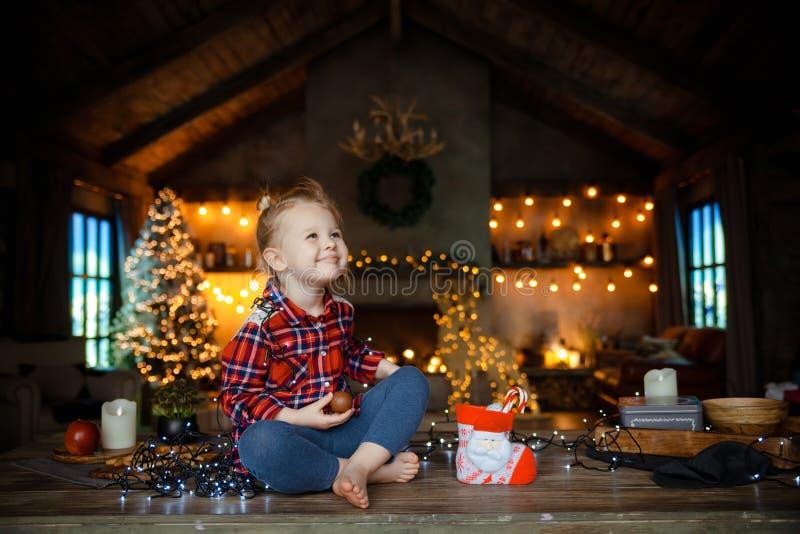 Menina loura branca pequena que senta-se em uma tabela de madeira na sala de visitas do chalé, decorada para a sagacidade da árvo fotografia de stock royalty free