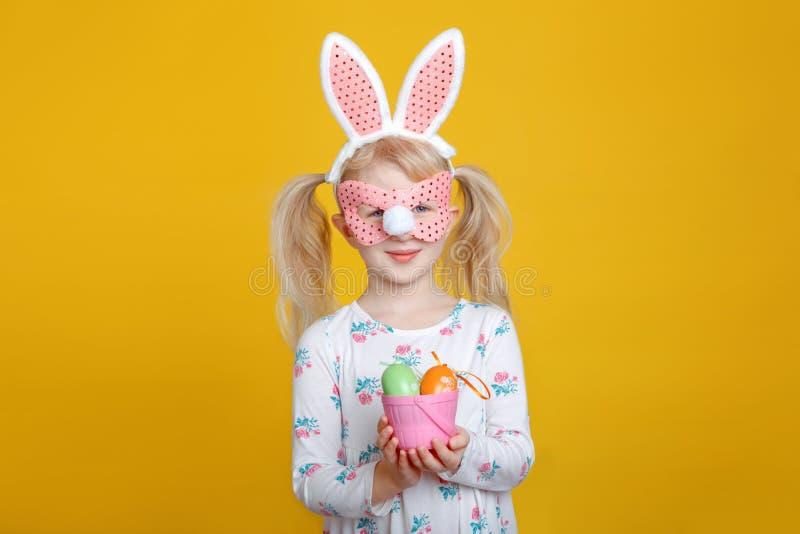 Menina loura caucasiano no vestido branco com as orelhas cor-de-rosa do coelhinho da Páscoa fotos de stock