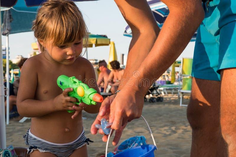 Menina loura caucasiano que joga na areia da praia no por do sol com uma arma de água plástica verde imagens de stock royalty free