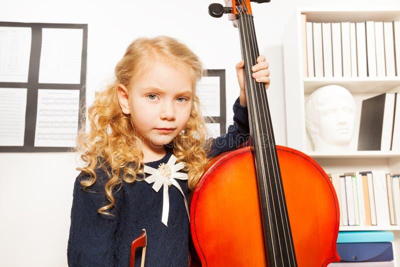 A menina loura com cabelo encaracolado guarda o violoncelo para jogar imagens de stock