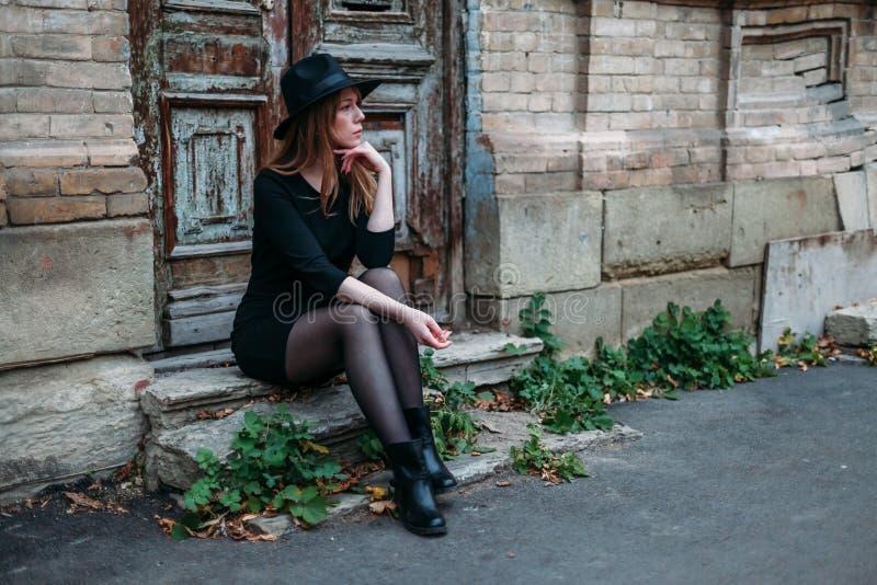 A menina loura com cabelo longo, no vestido preto no chapéu, está sentando-se nas etapas no fundo da porta de madeira velha antig imagens de stock royalty free