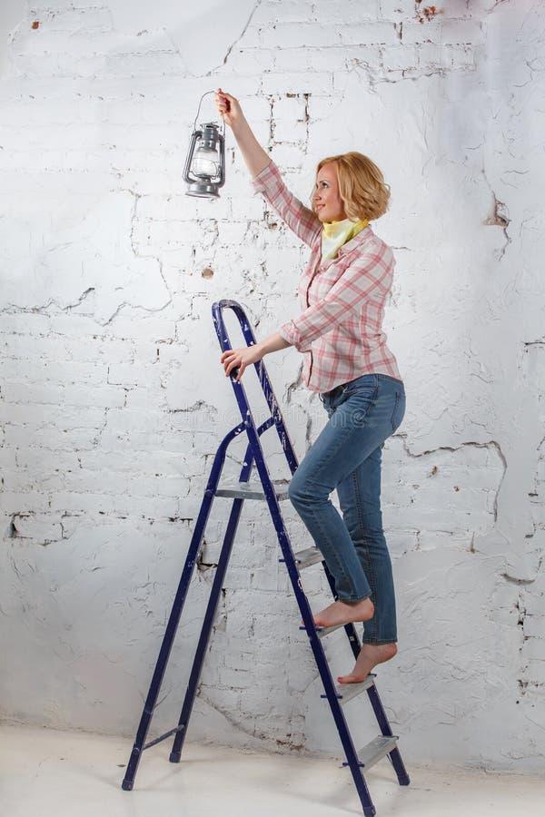 Menina loura com a lanterna leve que está na escada portátil fotografia de stock