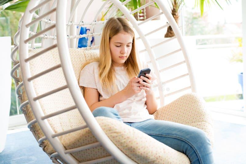 Menina loura com o telefone que senta-se na cadeira imagem de stock