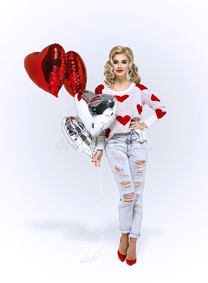 Menina loura com os balões de ar vermelhos dos corações foto de stock royalty free
