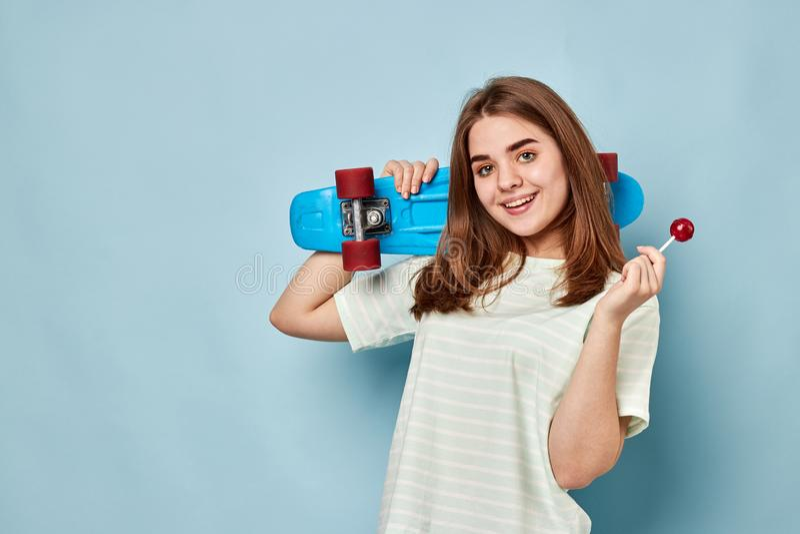 Menina loura com realizar dos chups do chupa em suas mãos um skate imagens de stock royalty free